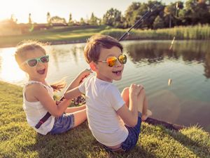 Happy young boy and girl wearing sunglasses and fishing.
