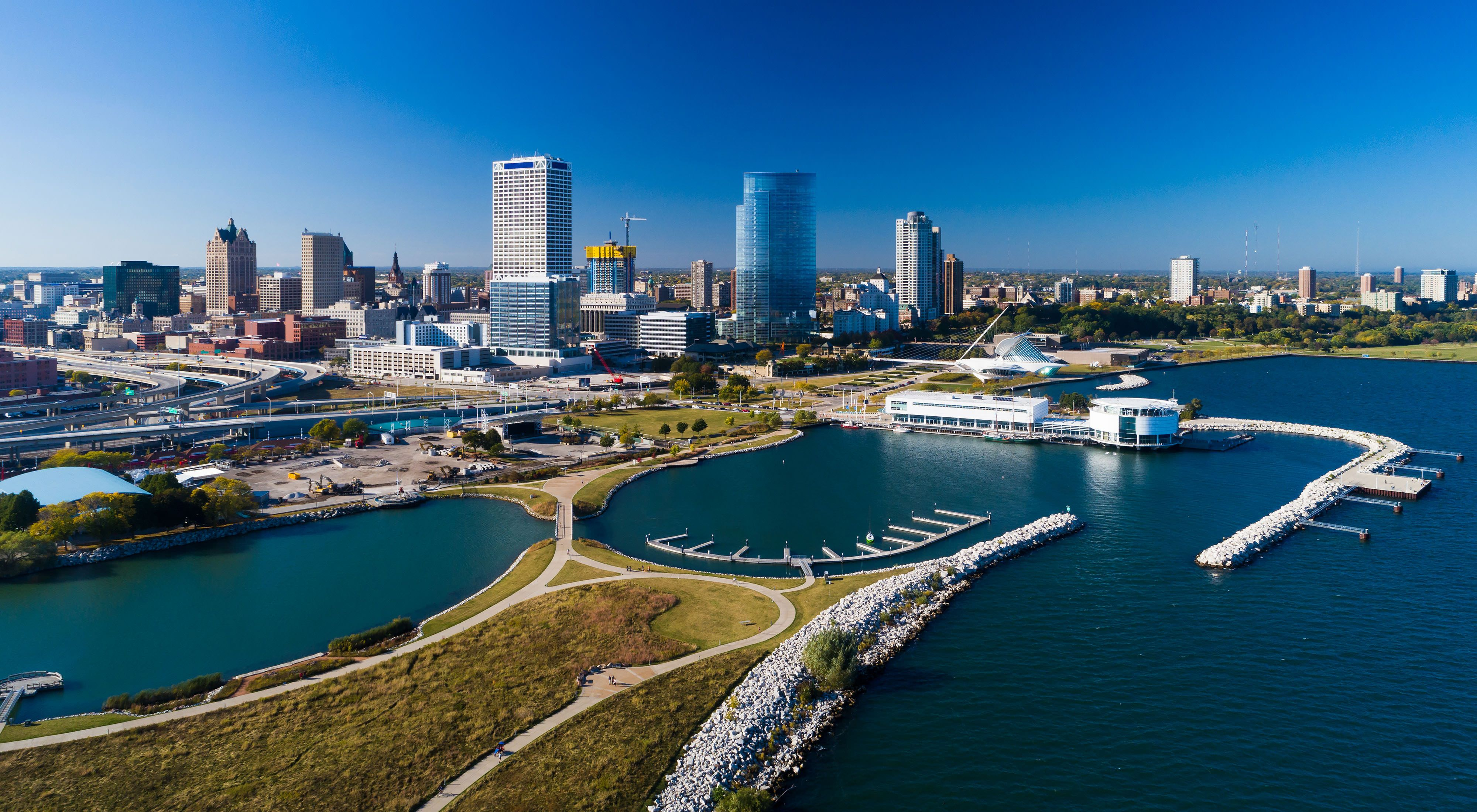 Aerial image of Milwaukee skyline on a blue sky day with Discovery World and Lakeshore State Park in the foreground.