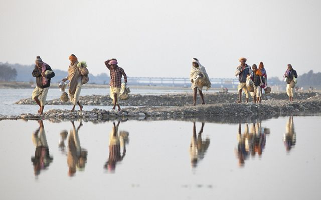 Villagers walk along the banks of the Ganges River in Haridwar.