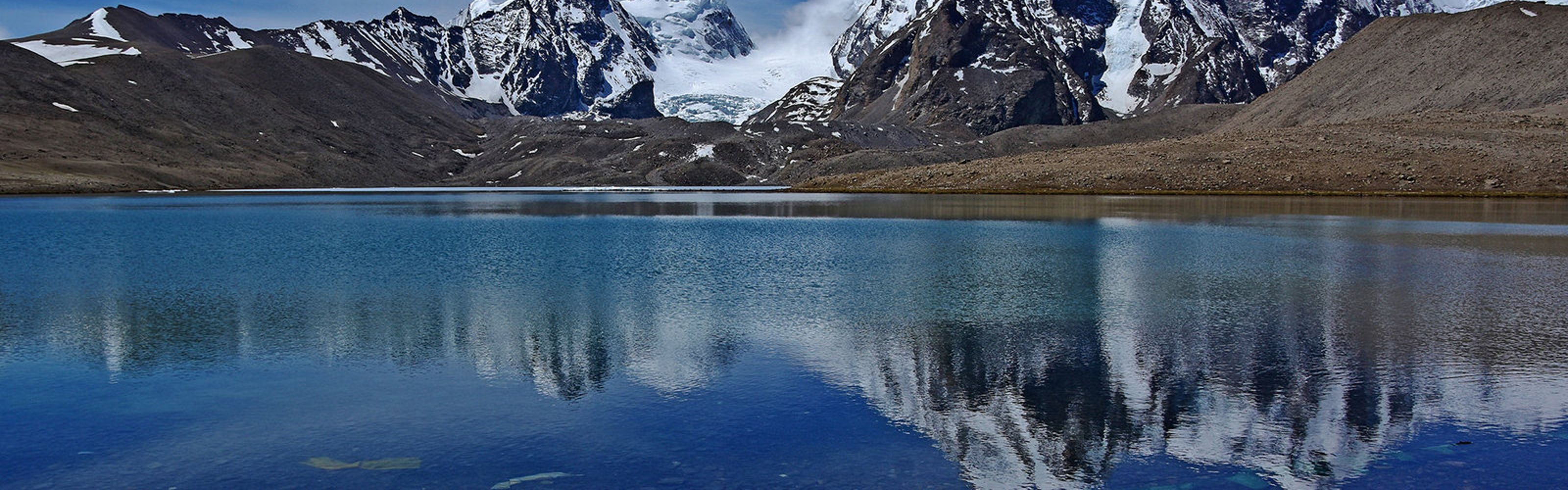 Gurudongmar Lake reflects mountains in the background in Sikkim, India.
