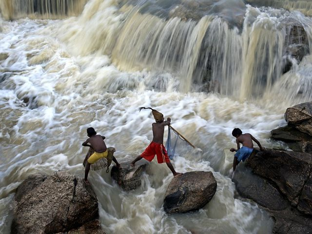 Rural children enjoy fishing after overnight heavy rainfall at a nearby culvert in West Bengal, India