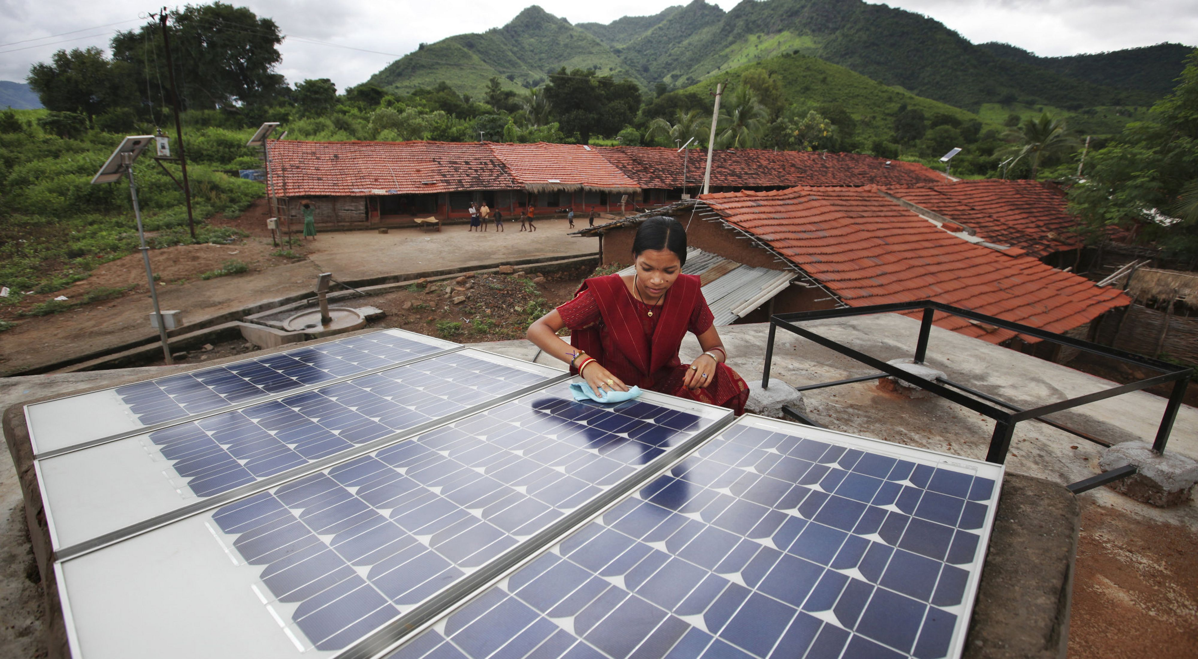 A person uses a cloth to clean solar panels on the roof of a village home in India.
