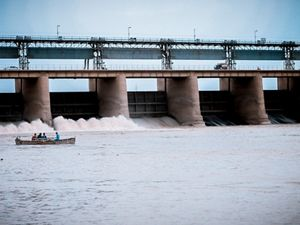 photo of a small boat near a hydropower dam in a river