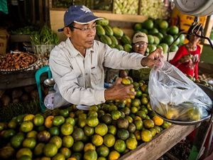 a man weighs fruit at a fruit stand