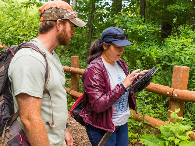 Young woman on trail with blue TNC cap on inputs information into a tablet she holds in her hand while man wearing a backpack observes.