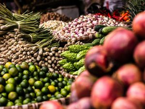 Large piles of vegetables on display at a fresh market