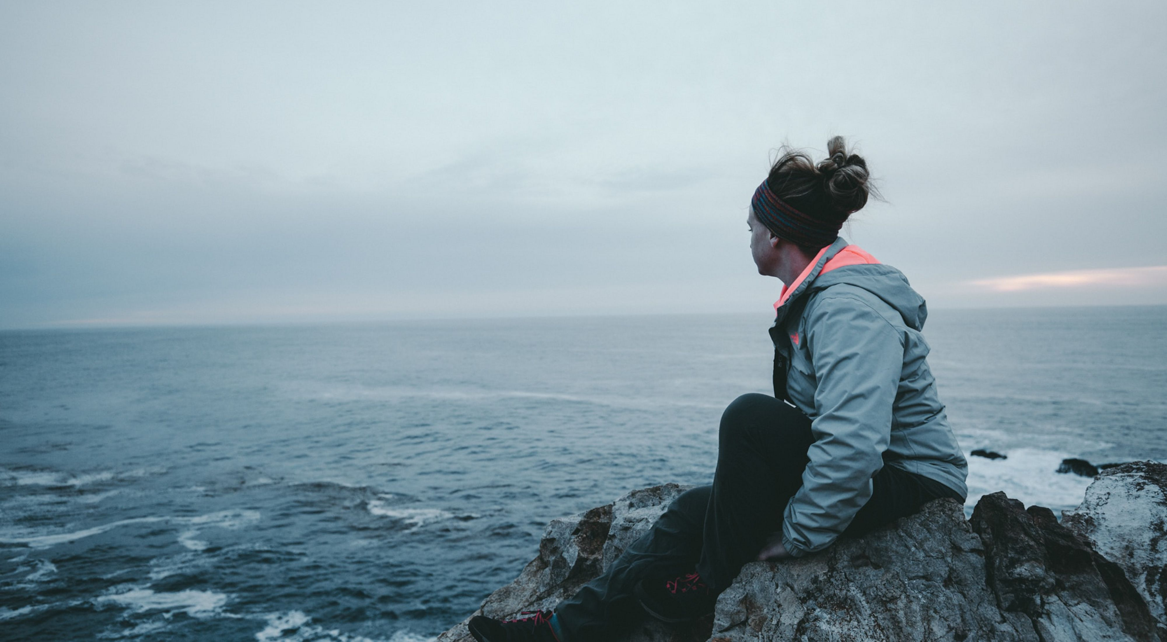 woman sits on rocky seashore looking out on ocean waves
