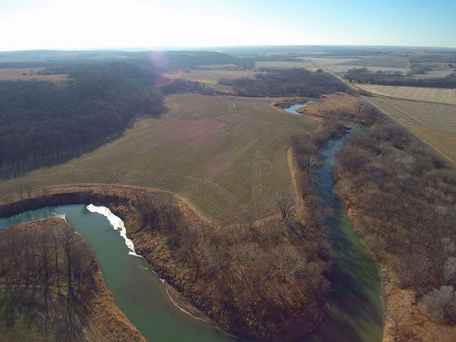 Aerial view of river winding through prairie fields and cultivated cropland.