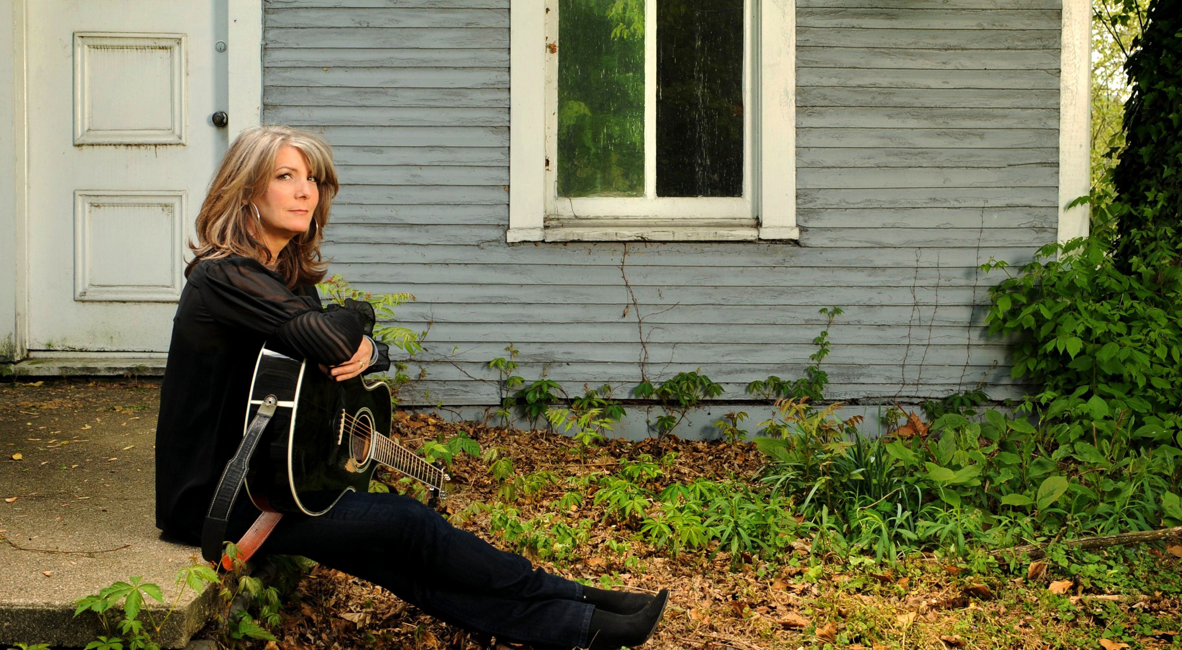 Kathy Mattea holding a guitar in her lap and sitting on a concrete walkway in front of an old house.