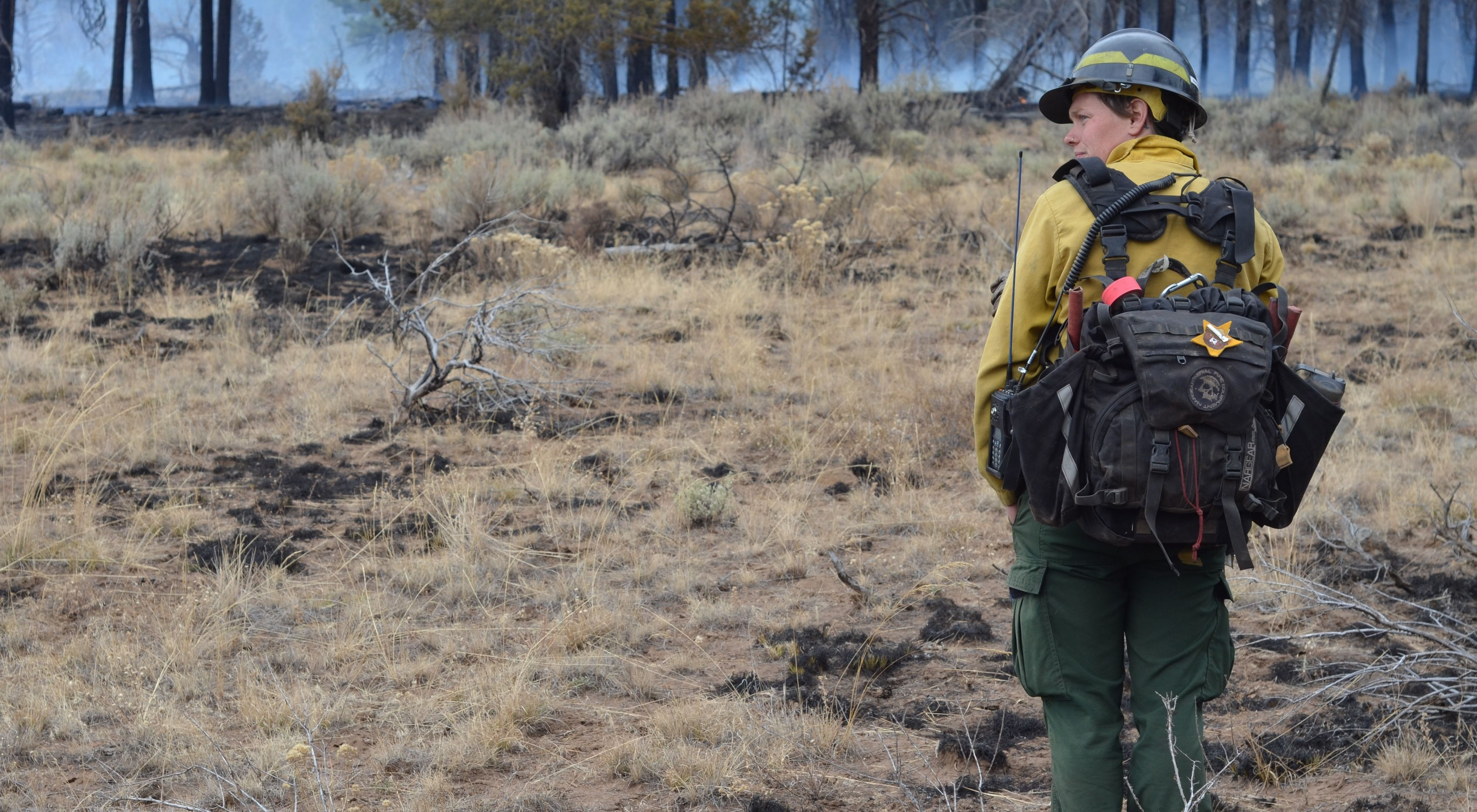 TNC Oregon Burn Boss Katie Sauerbrey stands in fire practitioner gear with her back turned and a forest in front of her.