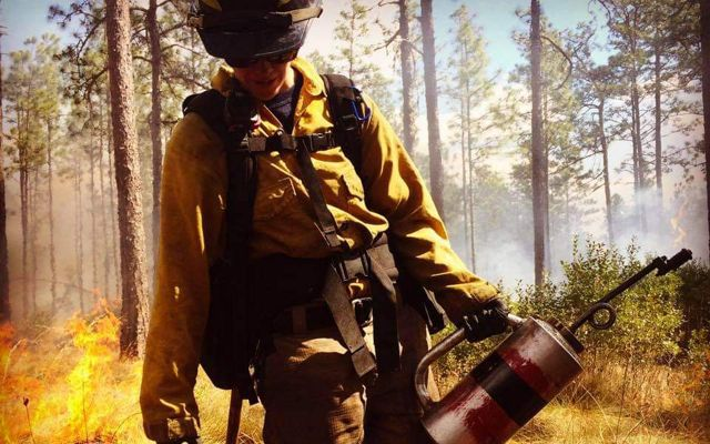 Katie Sauerbrey in fire gear holding a torch with trees and flames behind her.