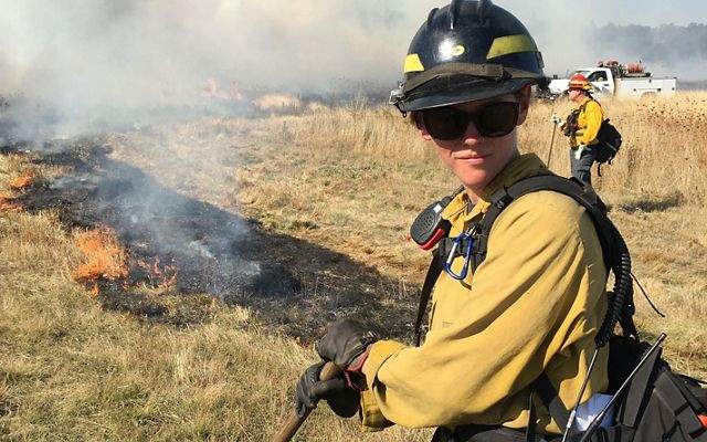 Katie Sauerbrey in fire gear standing in front of a line of burned, blackened grass.