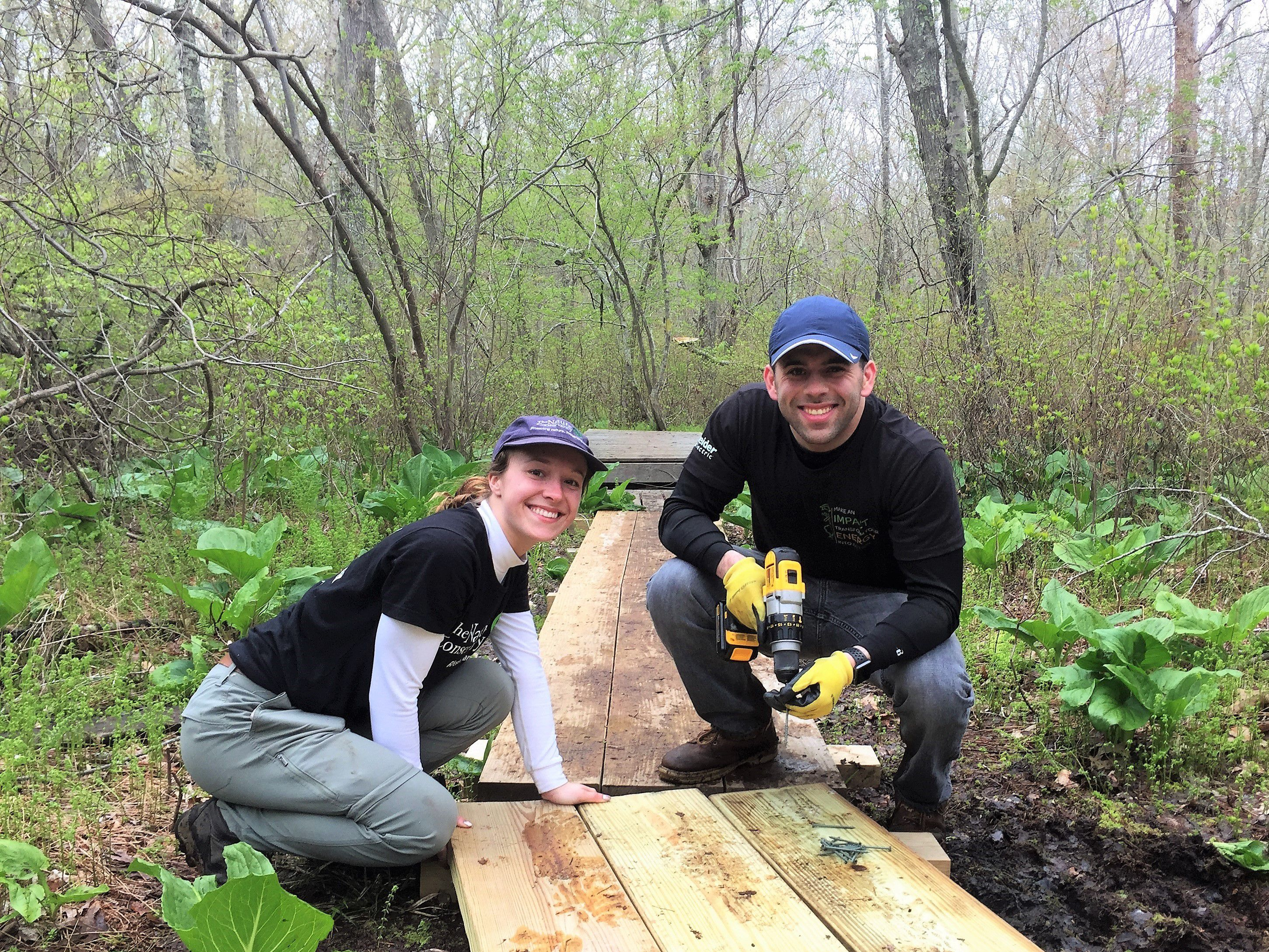 Two volunteers crouch over a newly built footbridge on a muddy wooded trail.