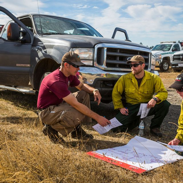 September 2015. Jeff Crandall (left) and Oregon Fire Manager (far right) plan the day's controlled burn in Kingston Preserve in Oregon.