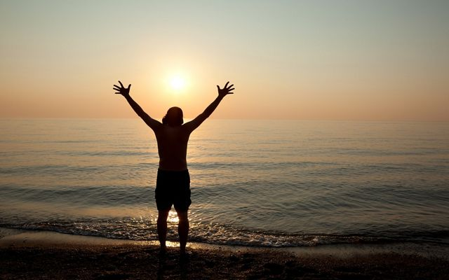 A silhouette of a man with his arms outstretched as he rejoices in the beauty of a sunset over Lake Erie.