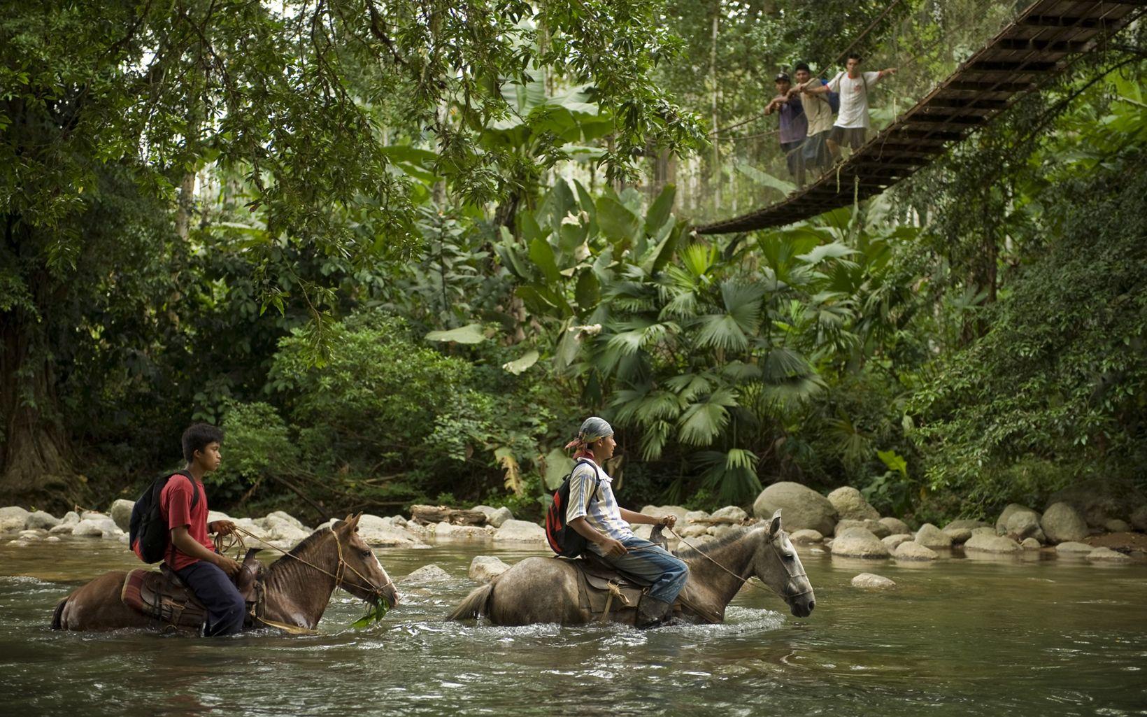 jovenes en caballo en u río en Costa Rica