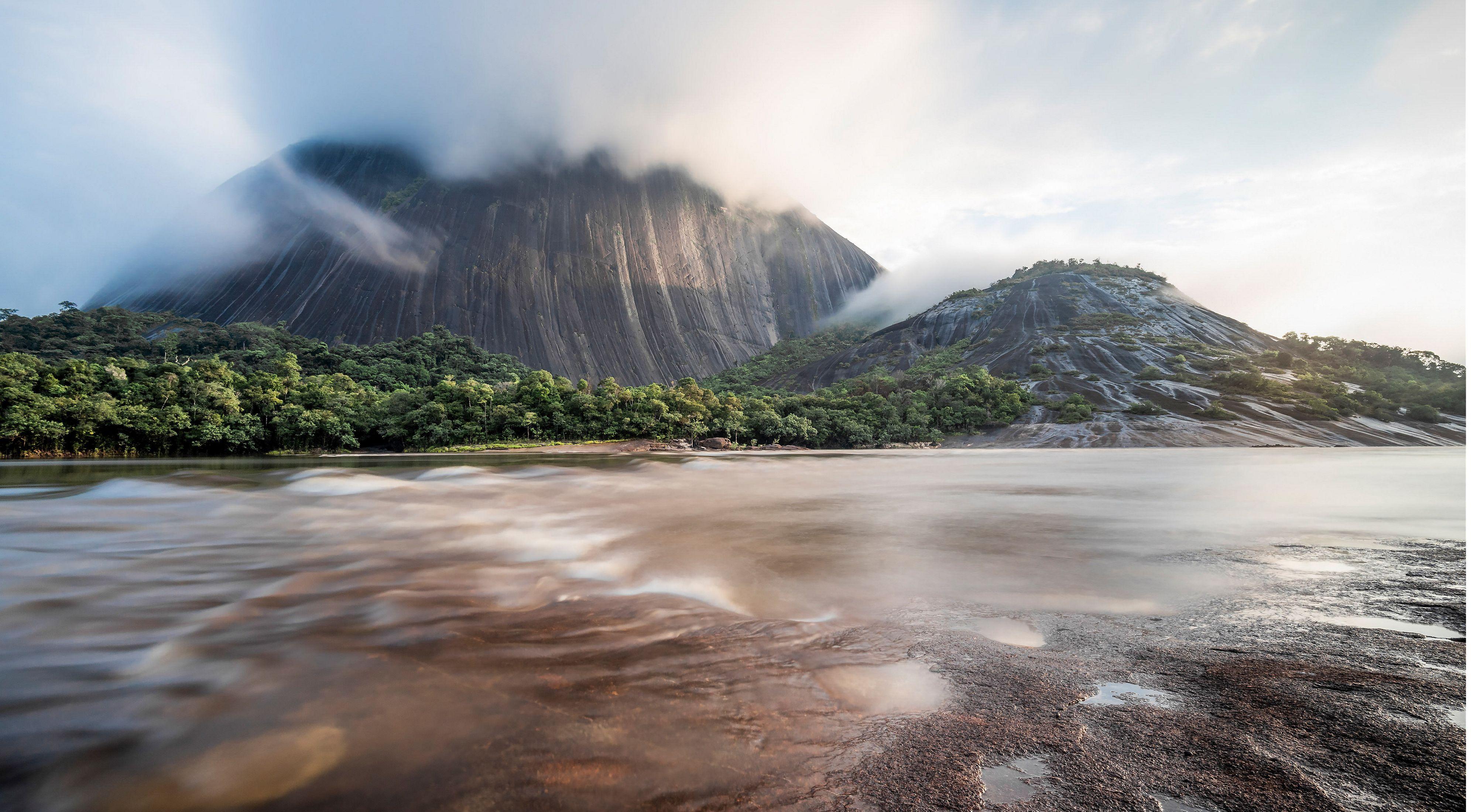 Realice esta fotografía la mañana del 18 de abril del 2019, mientras la neblina empezaba a elevarse cubriendo la punta del cerro ''Pajarito'', decidí capturar una larga exposición donde se observara el paso del agua en el río Inirida y el pasar de la neblina hacia el cielo.