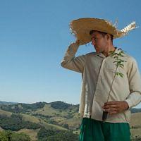 un hombre con sombrero sostiene una planta