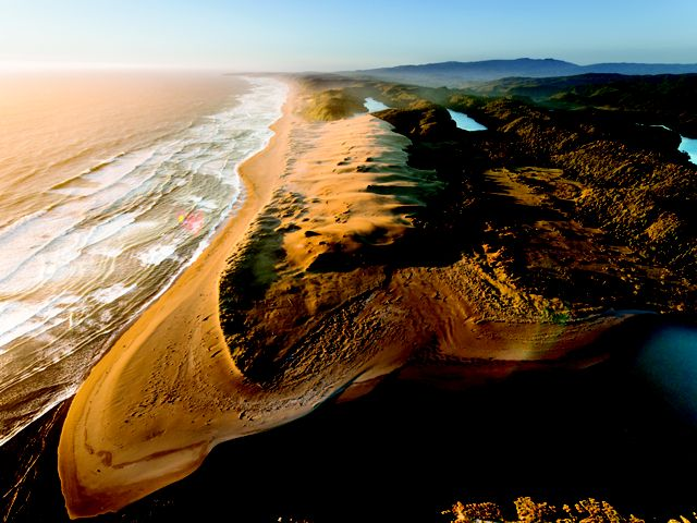 An aerial view of Colun Beach, sand dunes and the Colun River in the Valdivian Coastal Reserve, Los Rios, Chile.