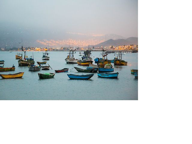 Small fishing boats float in the foreground near a dusky, electrified coastal mountain village