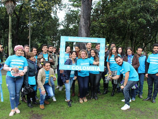 """Around 20 smiling people pose in neon blue shirts with #TheValueOfNature, some holding a sign reading """"Colombia"""""""