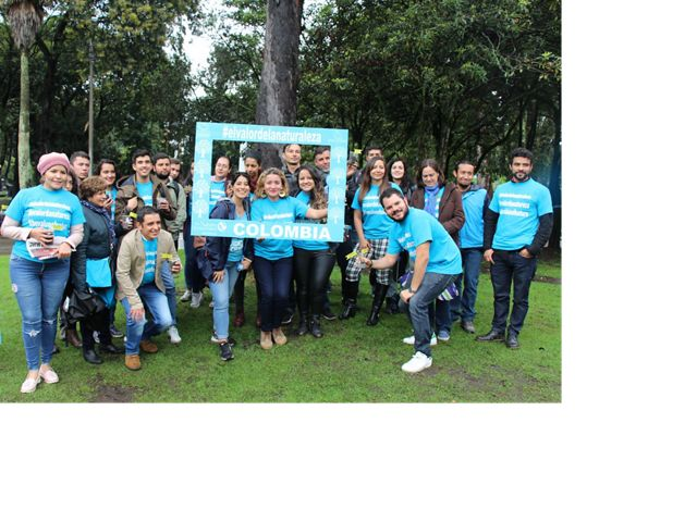 "Around 20 smiling people pose in neon blue shirts with #TheValueOfNature, some holding a sign reading ""Colombia"""