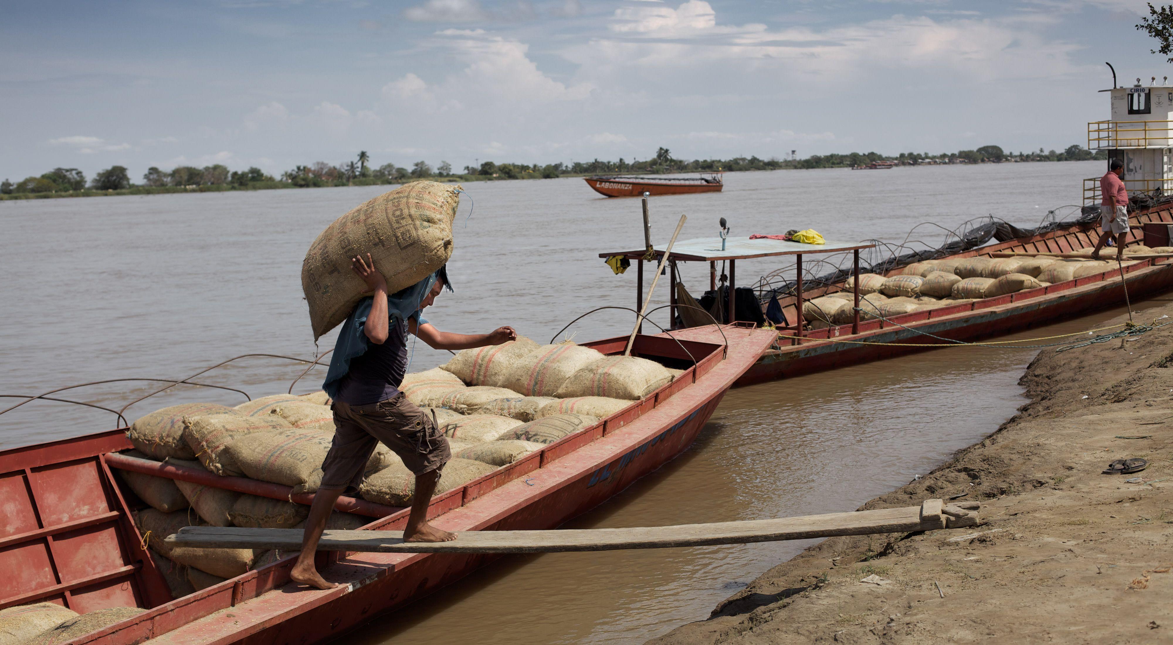 Un hombre descarga mercancías desde su bote en el río Magdalena en Colombia.