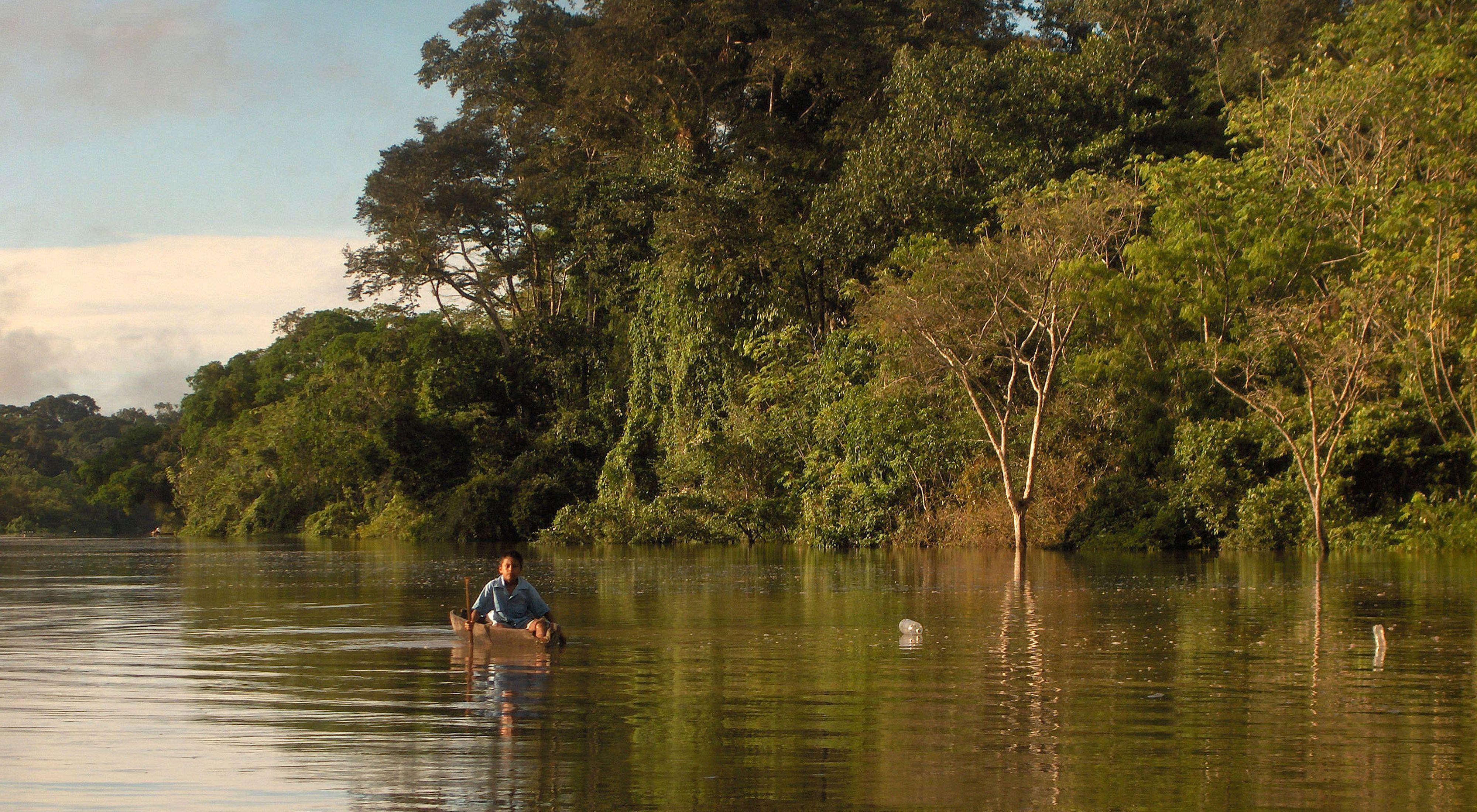 Un niño navega en un río del Amazonas