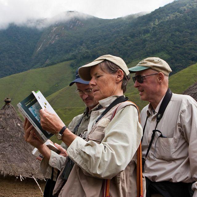 biólogos miran una guía de aves