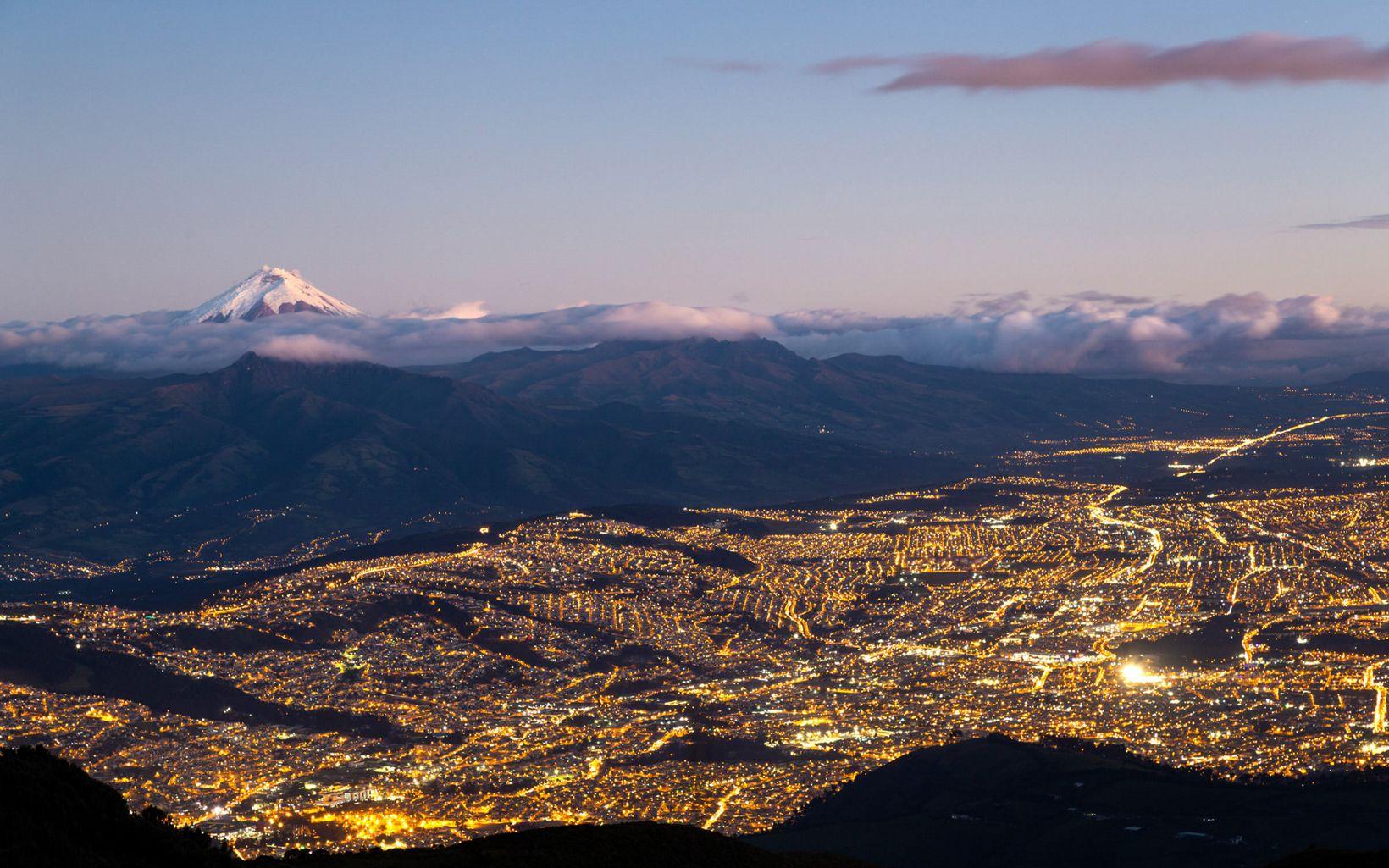 La ciudad de Quito. El atardecer ilumina al volcán  Cotopaxi
