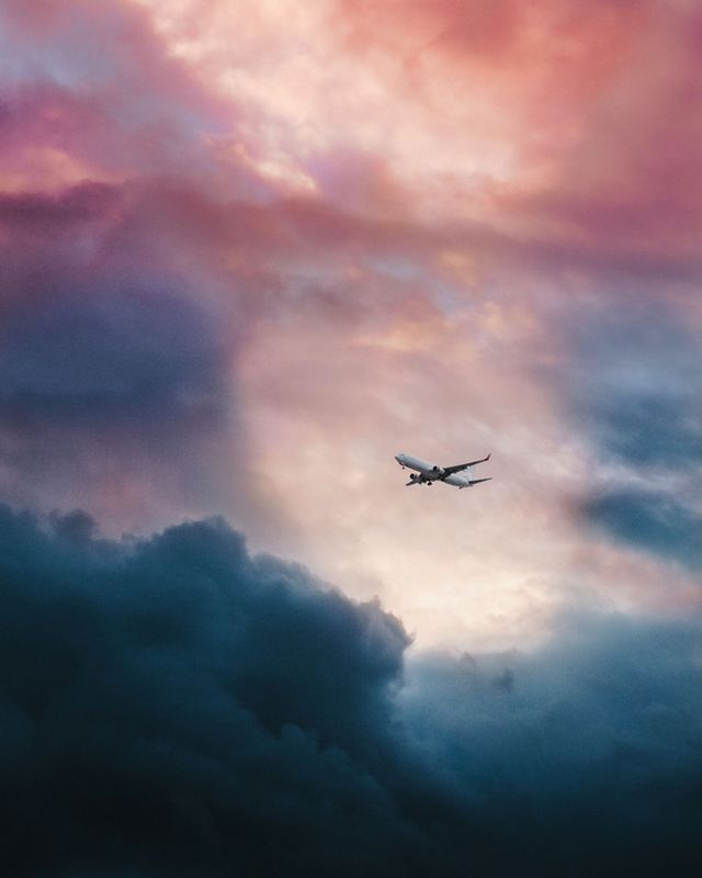 A commercial airplane flies through colorful skies.