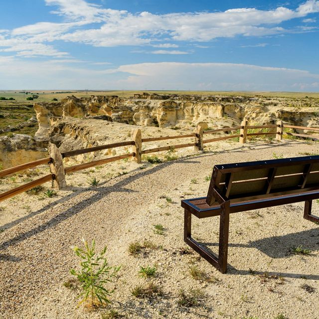 A wood bench sits at an overlook point at Little Jerusalem Badlands State Park on a clear day. In the distance is a view of rock formations and prairie.