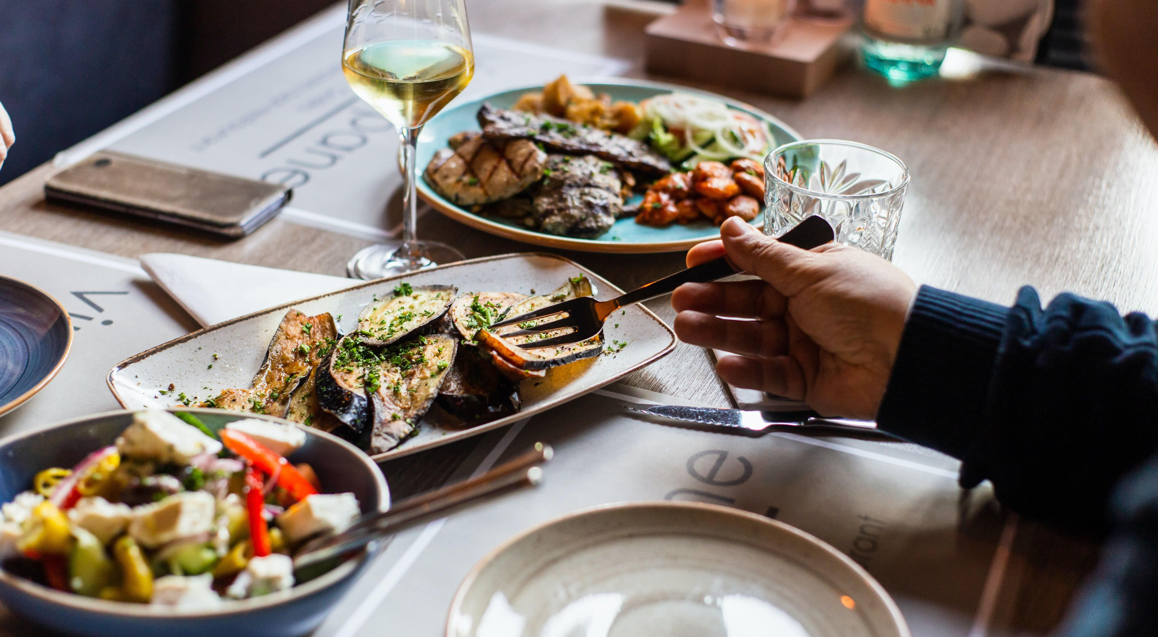 a person's arms pictured sitting at a dinner table with a variety of food on the table