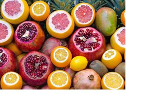 a colorful composition of sliced-open colorful citrus, pomegranates, mangoes and pineapples