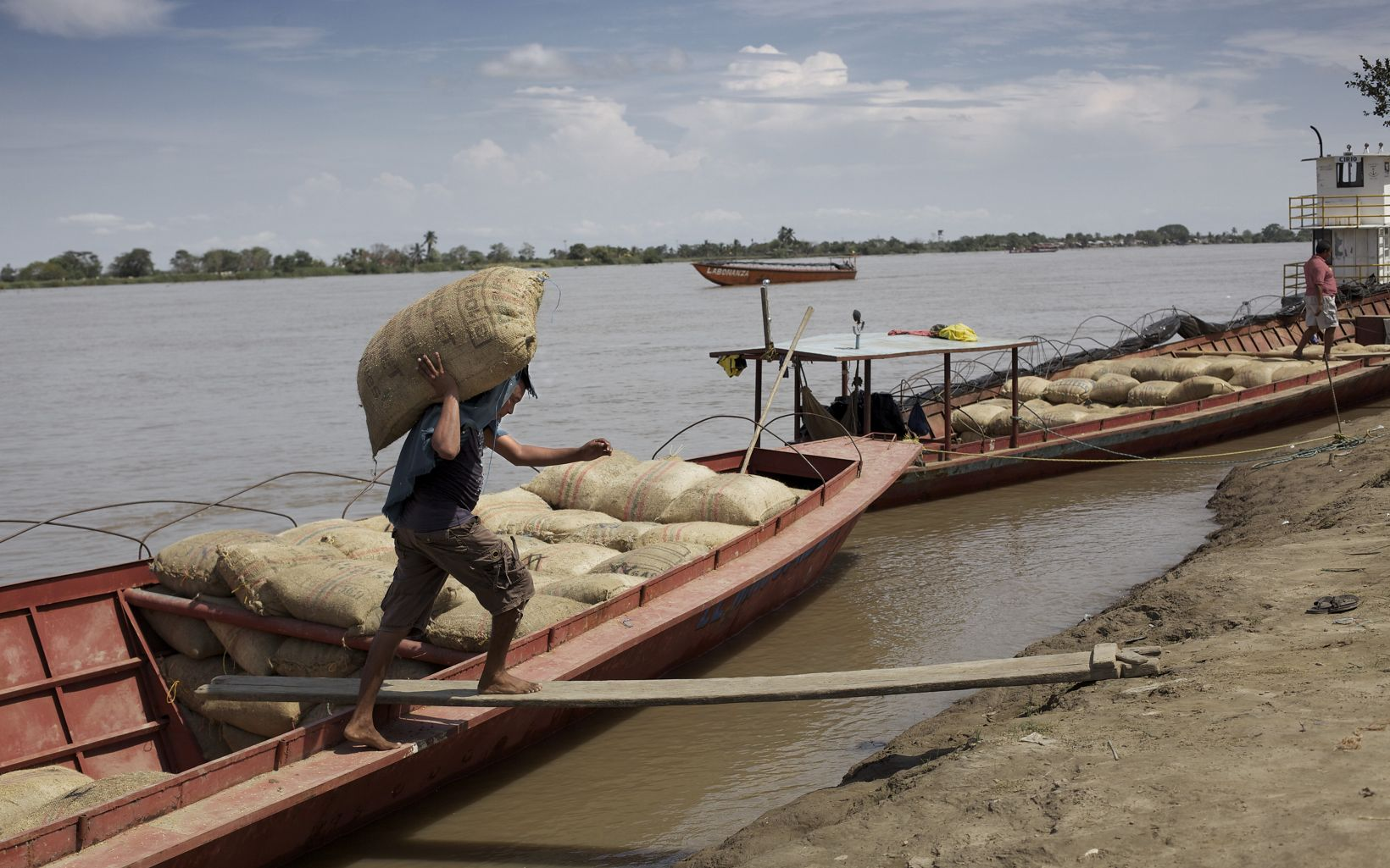 A man unloads goods from his boat on the Magdalena River in Colombia.