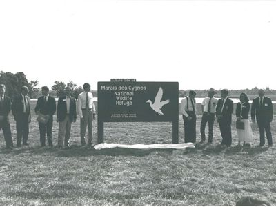 Nine men and 1 woman stands next to entrance sign.