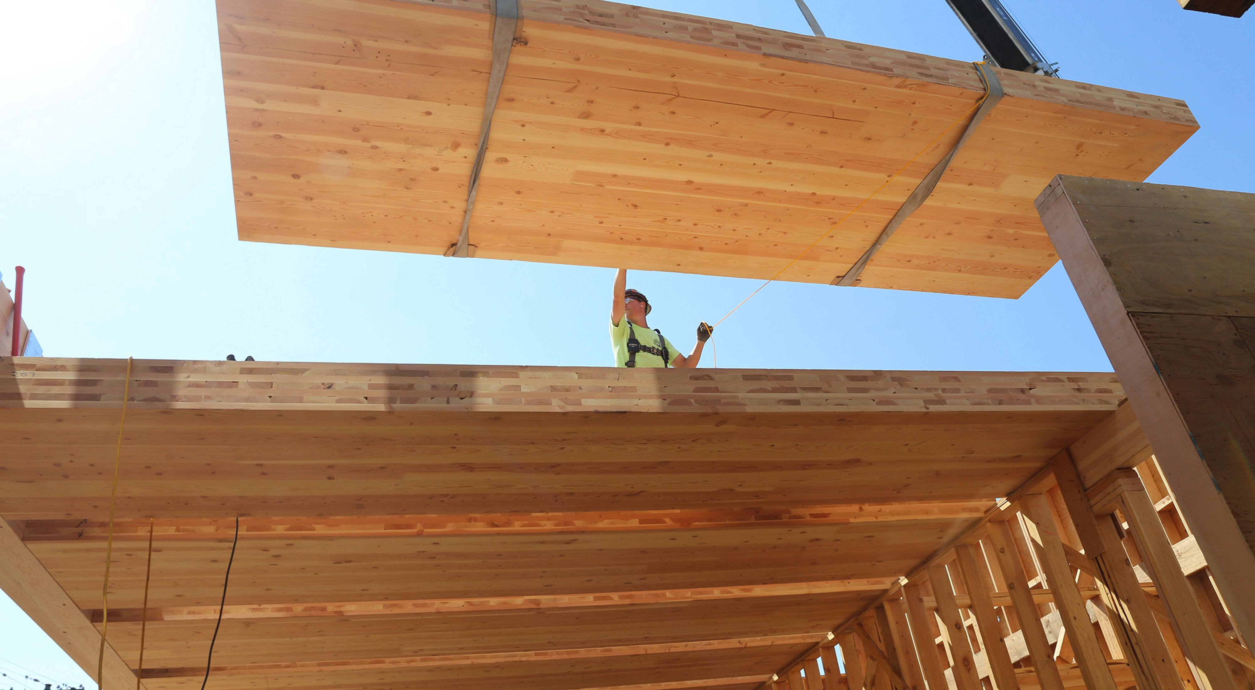 A construction worker helps guide the installation of cross-laminated timber for the Oregon Conservation Center in Portland, Oregon.