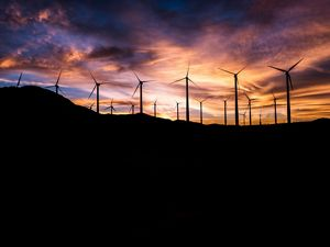 Wind turbines silhouetted against the sky at sunset.