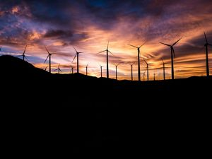 Wind turbines silhouetted against a colorful sky.