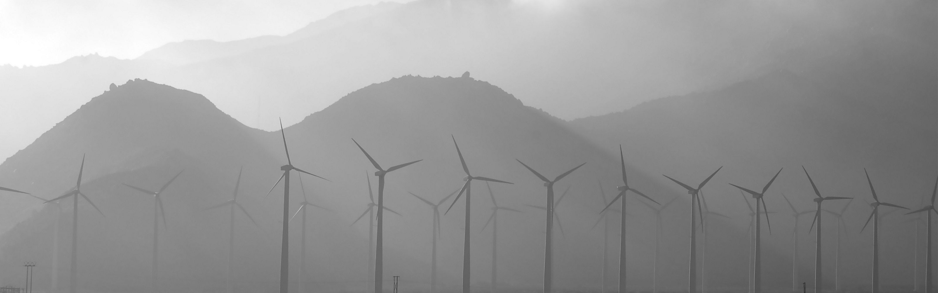 Wind turbines against a mountain backdrop