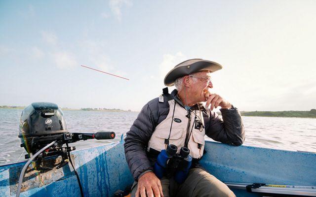 Man with binoculars sits on boat and looks toward horizon