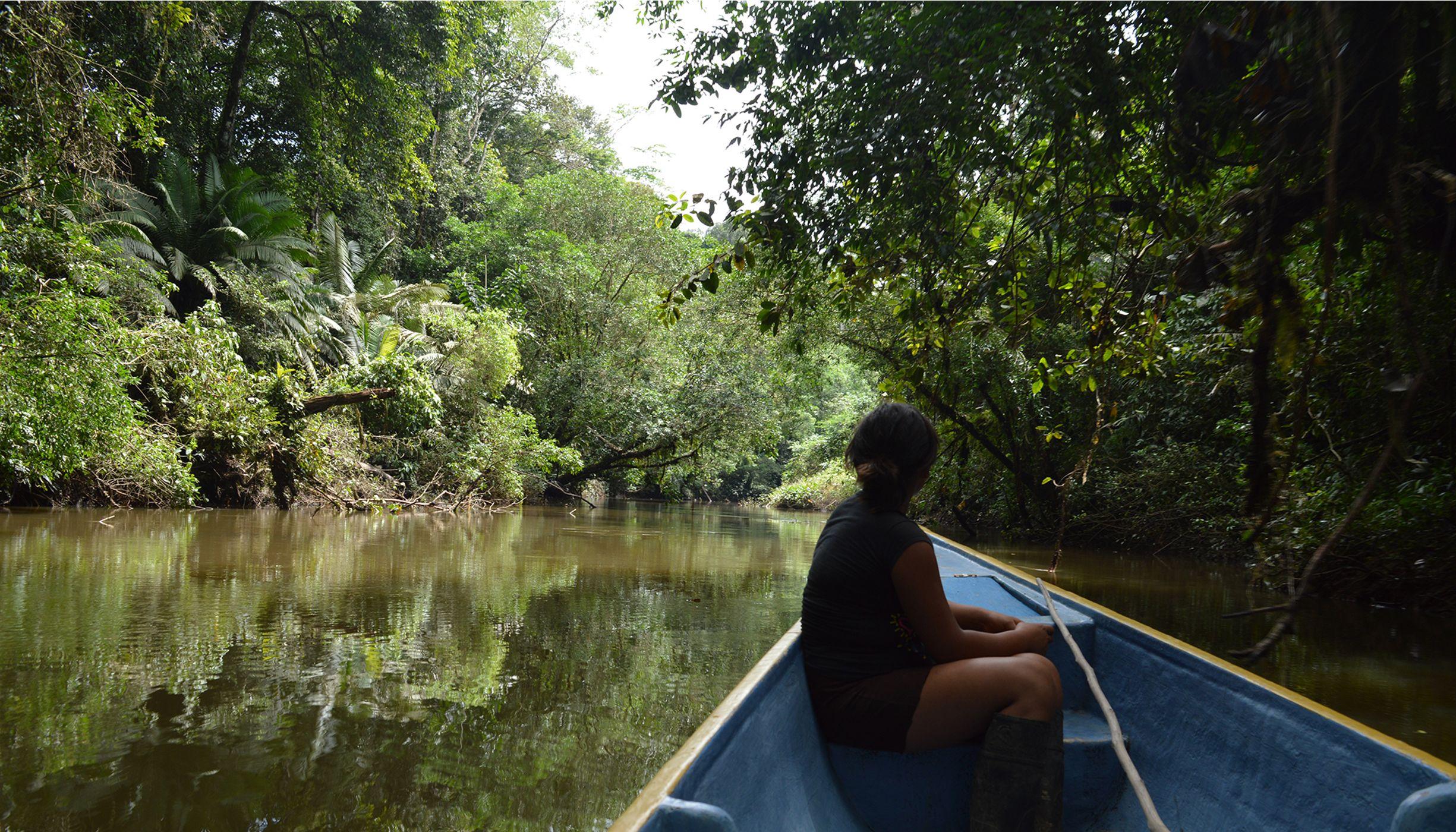 Mulher navegando em barco de um rio da Amazônia