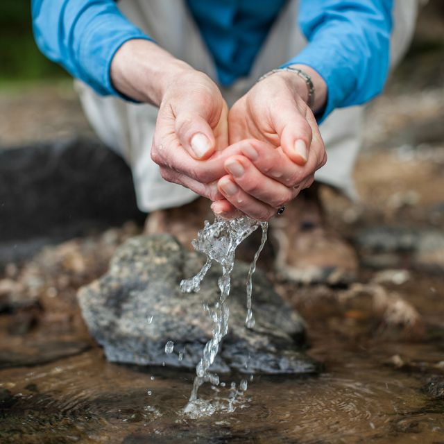 (ALL RIGHTS) July 2013. A woman scoops water with her hands.
