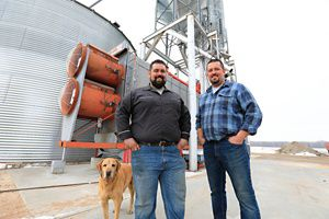 Two brothers stand with their grain feeder in the back