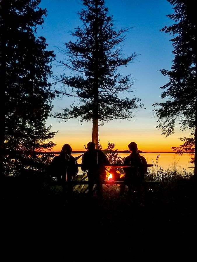 Three people sit at a picnic table by a campfire
