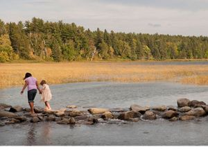Two children walk across the headwaters of the Mississippi River at Lake Itasca