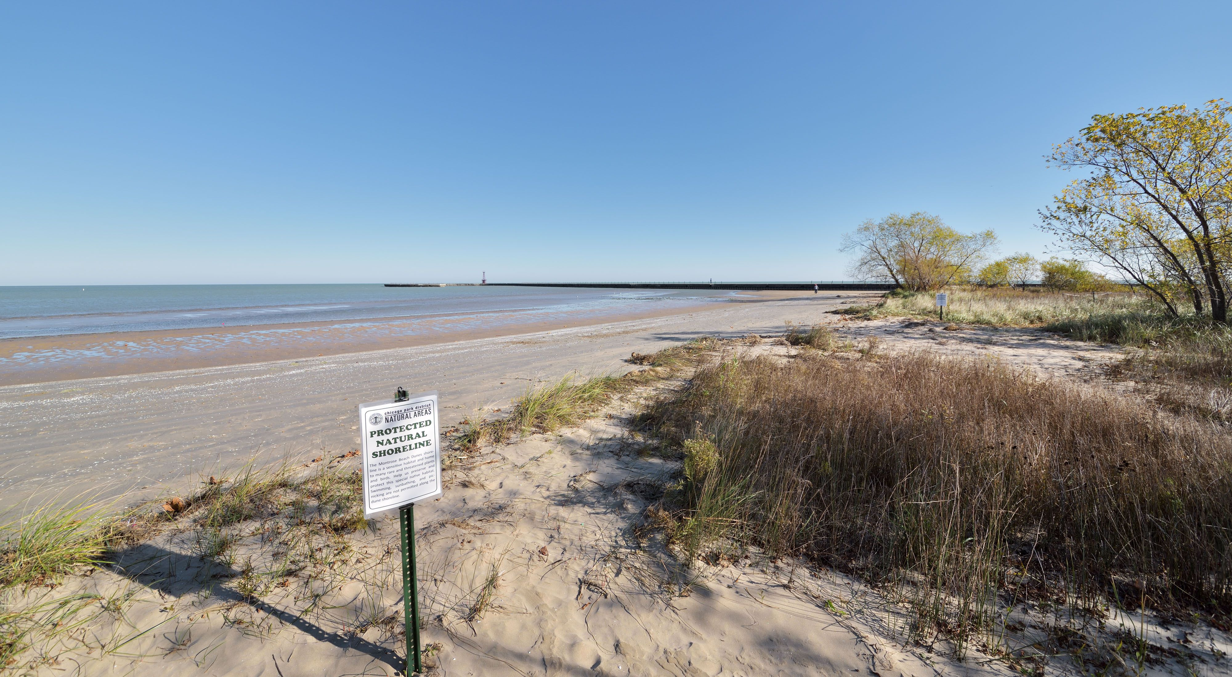 A protected shoreline sign stands along the edge of the water at Chicago's Montrose beach.