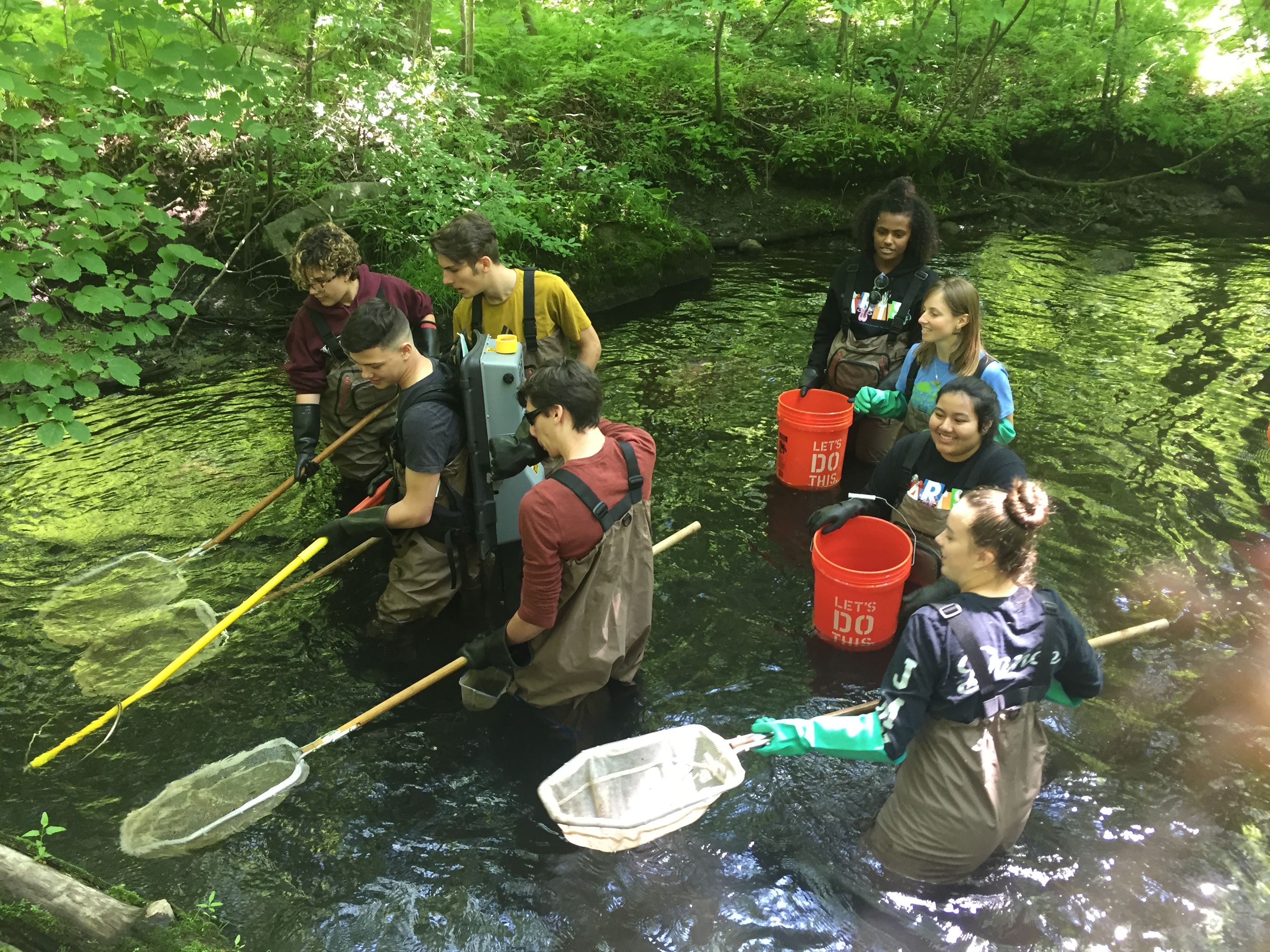 Eight youth in waders walk waist-deep in a river, with long-handled nets and buckets.