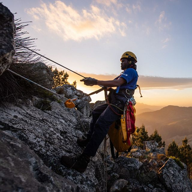 Mountain climber repelling over a ledge.