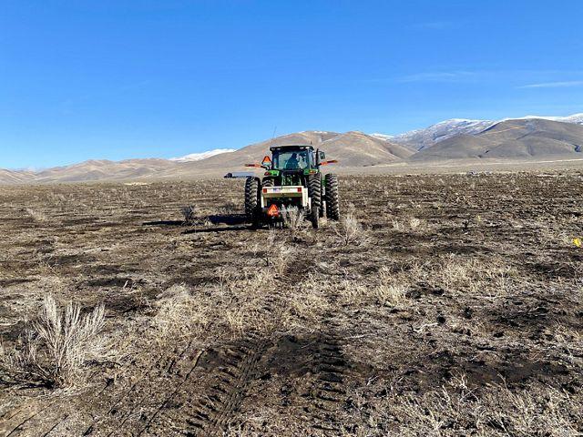 A tractor rolls across a landscape of dead grass.